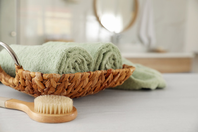 Wicker basket with rolled towels and massage brush on white wooden table in bathroom