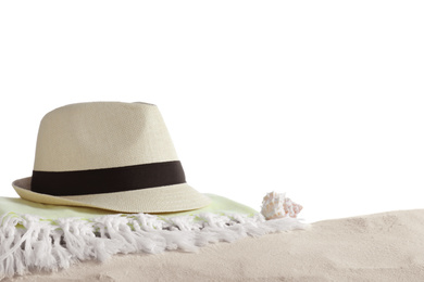 Folded towel, hat and shell on sand against white background. Beach objects