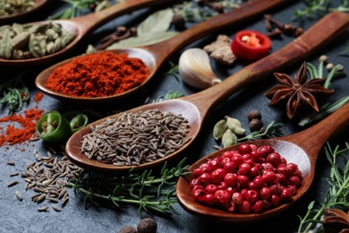 Different natural spices and herbs on black table, closeup