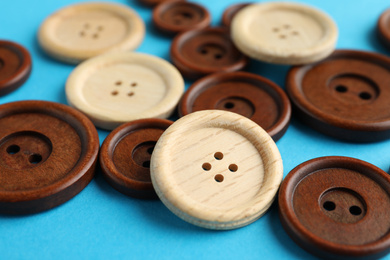 Many colorful sewing buttons on light blue background, closeup