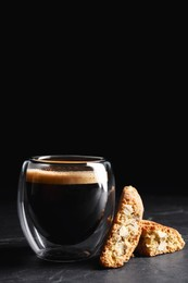 Tasty cantucci and cup of aromatic coffee on black table. Traditional Italian almond biscuits