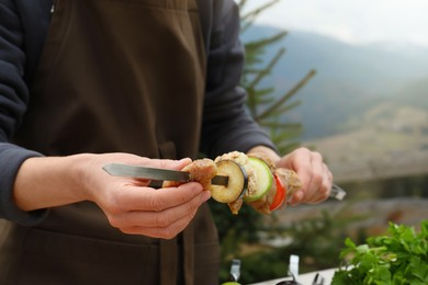 Woman stringing marinated meat and vegetables on skewer against mountain landscape, closeup