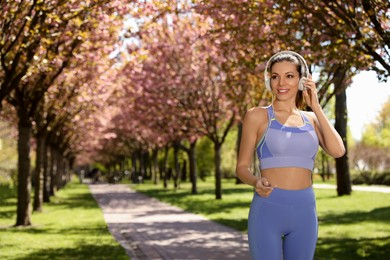 Woman with headphones on morning run in park, space for text. Fitness lifestyle