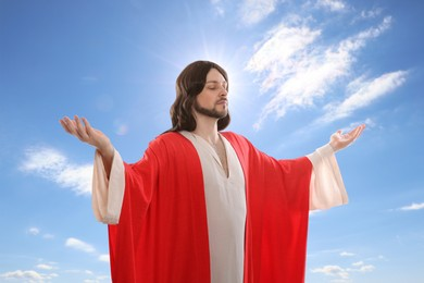 Jesus Christ with outstretched arms against blue sky