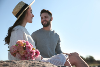 Happy young couple with flowers outdoors, focus on flowers. Honeymoon trip