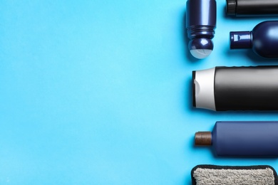 Flat lay composition with men's cosmetic products on light blue background. Space for text