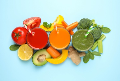 Delicious juices and fresh ingredients on light blue background, flat lay