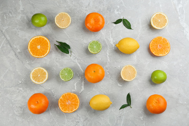 Flat lay composition with tangerines and different citrus fruits on grey marble background