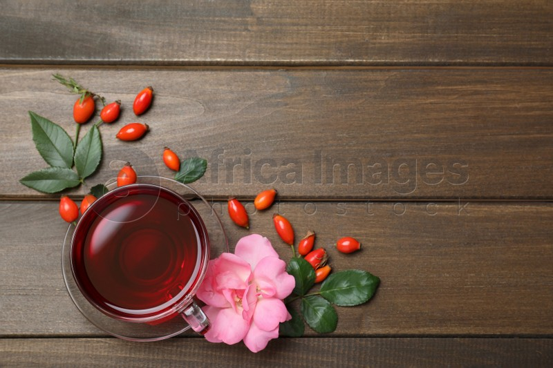 Flat lay composition with aromatic rose hip tea on wooden table. Space for text