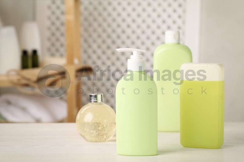 Bottles of shower gel on white wooden table in bathroom, space for text