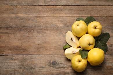 Fresh ripe organic quinces with leaves on wooden table, flat lay. Space for text