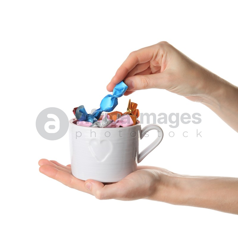 Woman taking candy in light blue wrapper from cup isolated on white, closeup