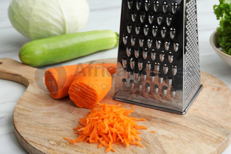 Grater and fresh ripe carrot on wooden board, closeup