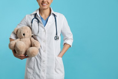 Pediatrician with teddy bear and stethoscope on turquoise background, closeup. Space for text
