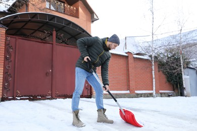 Young man shoveling snow outdoors on winter day