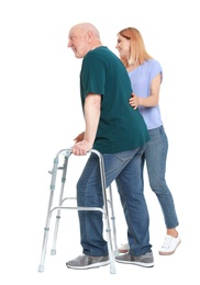 Caretaker helping elderly man with walking frame on white background