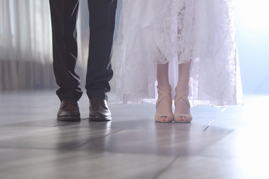 Newlywed couple in festive hall, closeup of legs