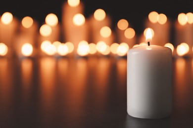Burning candle on black table, space for text. Memory day