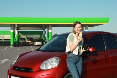 Beautiful young woman with coffee eating hot dog near car at gas station