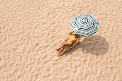 Woman resting in sunbed under striped beach umbrella at sandy coast, space for text