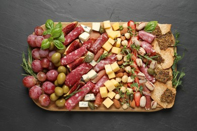 Different tasty appetizers on dark grey table, top view