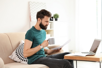 Young bearded man with coffee and documents working on sofa at home