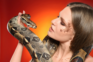 Beautiful woman with boa constrictor on bright colorful background, closeup