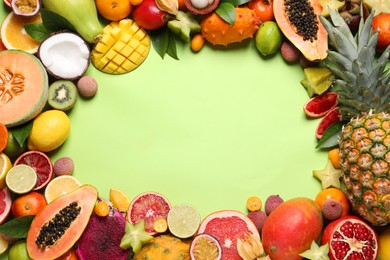 Frame of different exotic fruits on green background, flat lay. Space for text