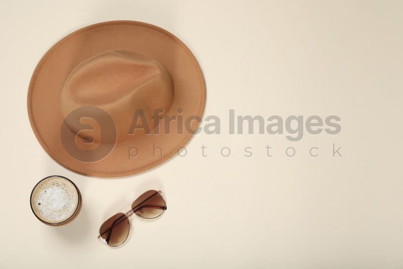 Stylish hat, sunglasses and coffee on beige background, flat lay. Space for text