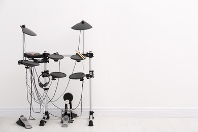 Modern electronic drum kit near white wall indoors, space for text. Musical instrument