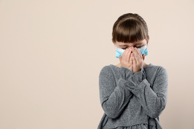 Little girl in medical mask on beige background, space for text. Virus protection