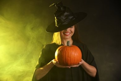Young woman wearing witch costume with pumpkin in smoke cloud on dark background. Halloween party
