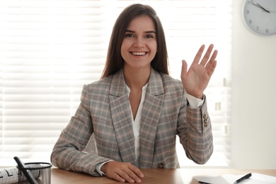 Young woman talking to her coworkers through video conference in office, view from webcam