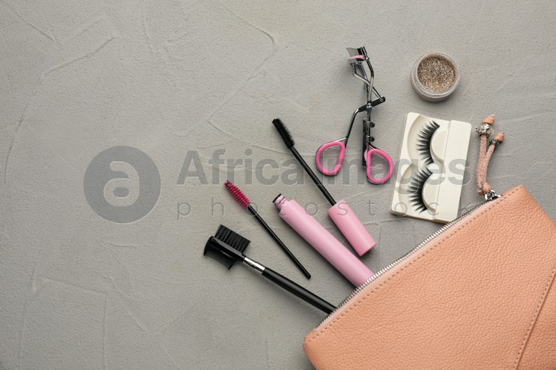 Flat lay composition with eyelash curler, makeup products and accessories on grey table. Space for text
