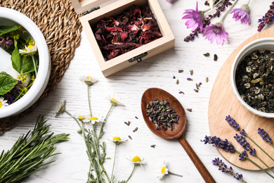 Flat lay composition with healing herbs on white wooden table
