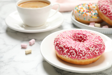 Yummy donut with sprinkles and coffee on white marble table