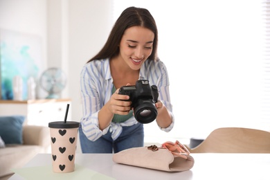 Young photographer taking picture of accessories indoors, focus on camera