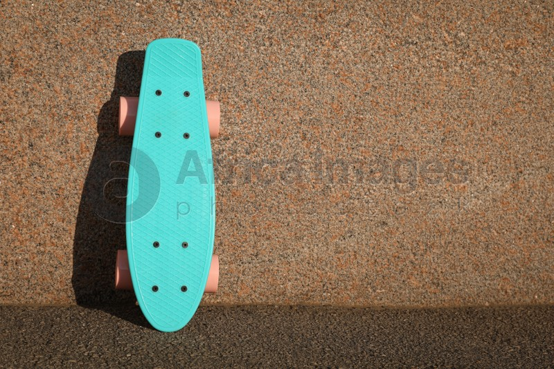 Light blue skateboard with pink wheels near wall outdoors. Space for text