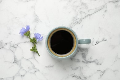 Cup of delicious chicory drink and flowers on white marble table, flat lay