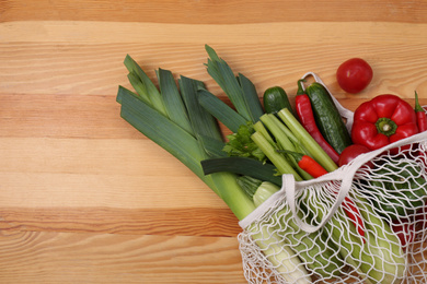 Net bag with vegetables on wooden background, top view