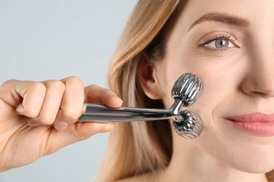 Young woman using metal face roller on light grey background, closeup