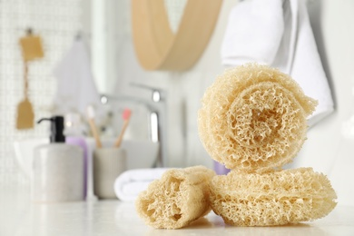 Natural loofah sponges on table in bathroom. Space for text