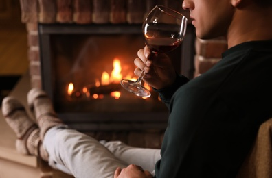 Man with glass of wine near fireplace at home, closeup