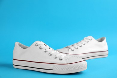 Pair of trendy sneakers on light blue background