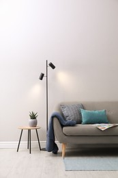 Stylish room living interior with comfortable sofa and lamp near white wall