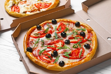 Cardboard boxes with tasty pizzas on wooden table