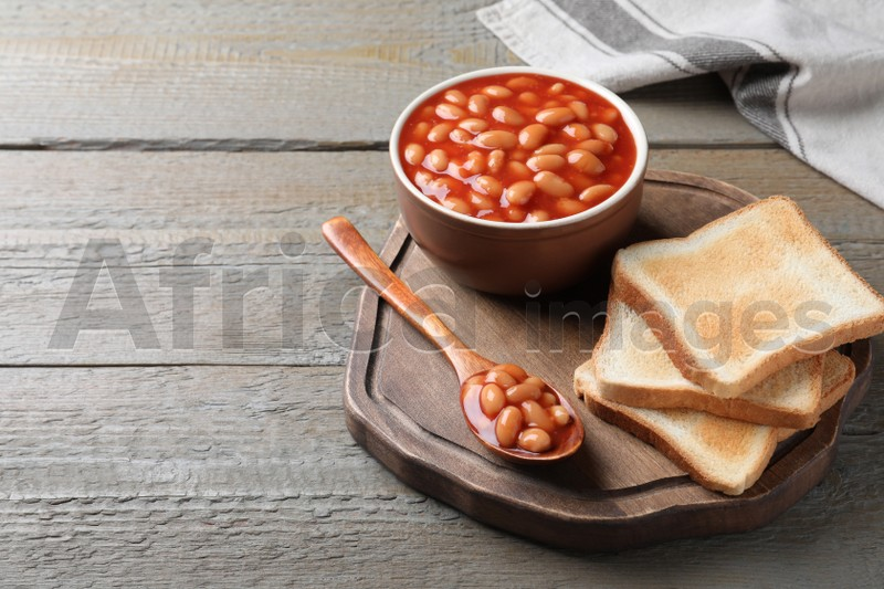 Toasts and delicious canned beans on wooden table, space for text