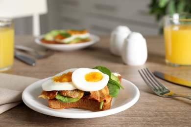 Sandwich with egg, bacon and spinach served on wooden table