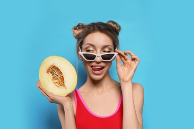 Young woman with fresh melon on light blue background. Exotic fruit