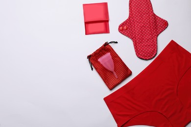 Women's underwear, disposable and reusable female hygiene products on white background, flat lay. Space for text